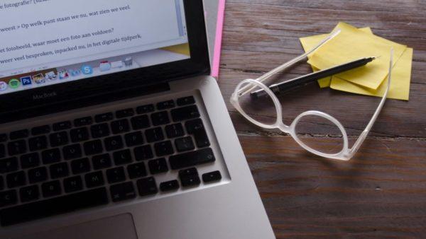 Beeld bij de scriptie challenge laptop met tekst, bril en post-its