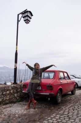 Andrina Sol blije pose bij rode auto in Ohrid