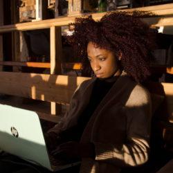 Studente geconcentreerd aan het werk met het zonlicht op haar gezicht