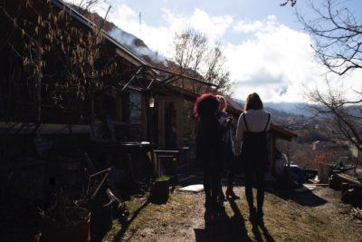3 mensen staan buiten met een kop koffie, op de achtergrond houten huisje met rokende schoorsteen